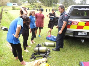 Fireman teaching students how to use gas masks.